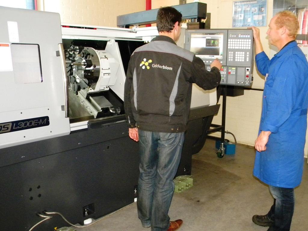 Gerard Rolleman (instructeur van Gelderblom) en André Heijne (praktijkdocent RTC Metaal) programmeren een werkstuk aan de machine