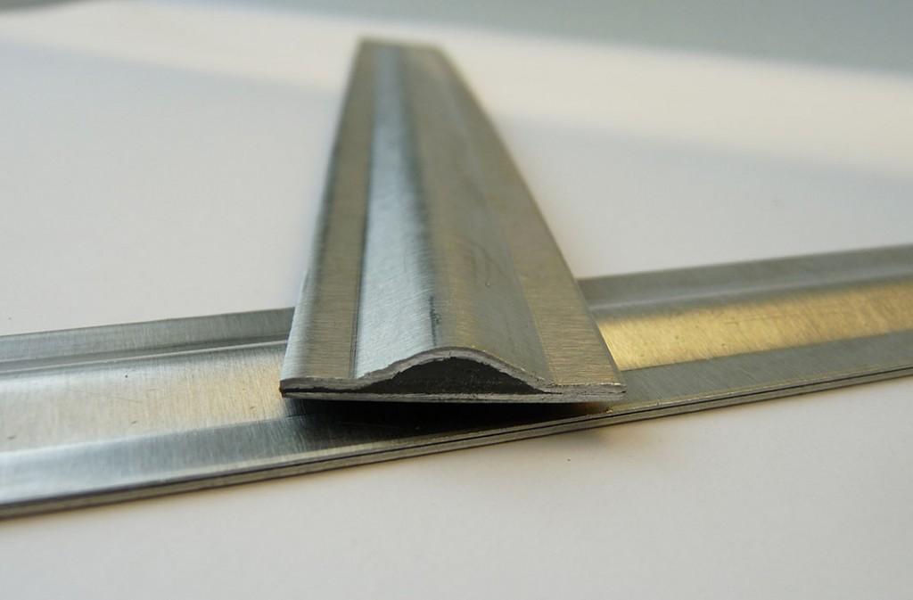 Deze strip toont een doorsnede die eenzijdig gebogen is. De zwarte vulling is de visco-elastische lijmlaag die tevens voor geluidsdemping zorgt (foto: Institut für Umformtechnik (IFU), Universität Stuttgart)