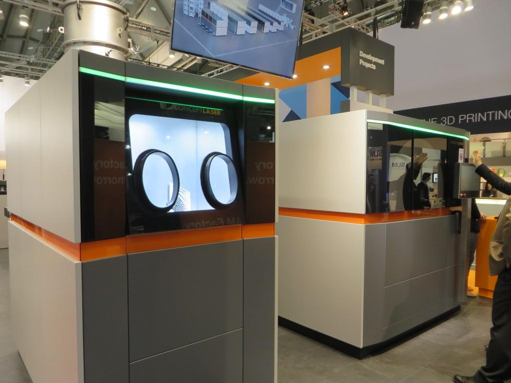 Concept Laser presenteerde in Frankfurt een gedeelte van een modulaire lijn voor AM (of een fabriek voor AM) waarvan het laserstation (rechts op de foto) kan werken met vier lasers. De verschillende modules van de lijn bewegen naar en van het laserprocesstation (foto: Reinold Tomberg)