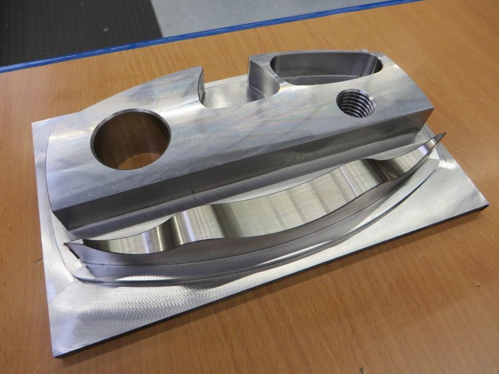 Het demonstratiewerkstuk van staal 52 aan de hand waarvan Hedelius de mogelijkheden van het vijfassig frezen zal demonstreren. Aan de bovenzijde is bijvoorbeeld een gleuf gefreesd met een diameter van 16 mm, een diepte van 20 mm en met een voeding van 600 mm/min